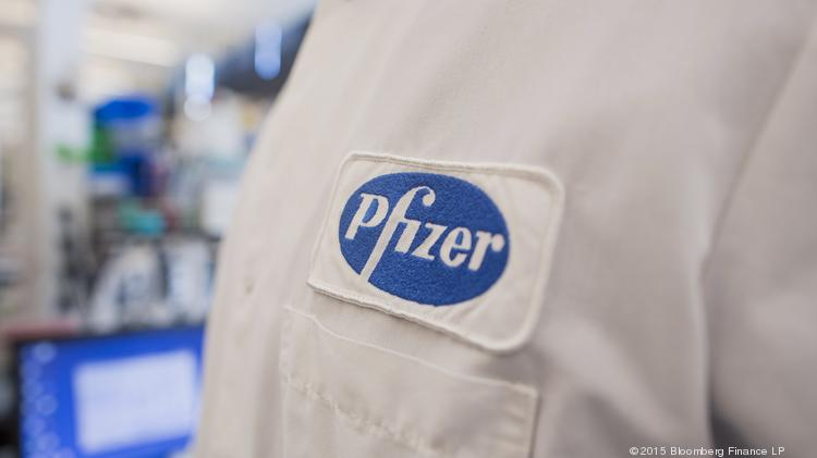 The Pfizer Inc. logo is seen on the lab coat of an employee at the company's research and development facility in Cambridge, Massachusetts, U.S., on Monday, Oct. 26, 2015. Pfizer is expected to report quarterly earnings on October 27. Photographer: Scott Eisen/Bloomberg
