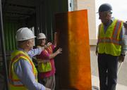 Kay Zafar, John Young of Yates Construction  and Mehrdad Moayedi look at a window finish that will be in a third-floor common area.