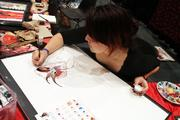 Nen, an artist, worked on a drawing at her booth at the 2013 FandomFest.