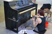 """Local artist Luzalma Gonzalez paints one of the FTL Play Your City pianos. The FTL Play Your City project was inspired by the success of other cities implementing similar projects to activate public spaces. Several painted """"traveling pianos"""" were set up in various locations around downtown Fort Lauderdale for a span of three months, inviting passers-by to sit and play a tune."""