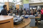 Carmen Diaz (far right), 13, sings and plays percussion with cups while being interviewed by Ryan Seacrest during the first broadcast from Seacrest Studios at the Levine Children's Hospital.