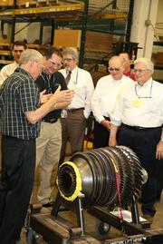 GE Aviation employees look at the compressor the company recently tested.