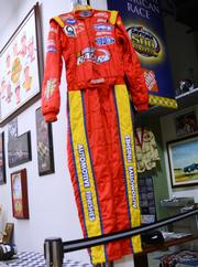 A race suit donated to the collection by Jeff Gordon hangs on a wall by the garage.