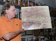 Eddie Roche holds an aerial photo of the Daytona International Speedway land prior to development in 1957. The track shown is actually Daytona Kennel Club.