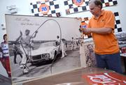 Eddie with a photo of a pit crew in action from the early days of Talladega Speedway.