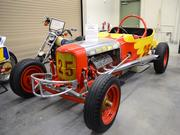A replica of a vintage Model T NASCAR Track Roadster is part of the garage display.