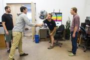 Alex Mondau,(center left) from Community Sourced Capital shakes hands with Andy Yatteau, (center right) Founder and COO of A & R Solar during a visit to their new location in SoDo in Seattle.  Also present is Dave Kozin, owner and CFO of A & R Solar (left) and Casey Dilloway, President and Director of Community Sourced Capital (right). A & R Solar raised almost $25,000 through 183 people through Community Sourced Capital so they could move to a larger space.