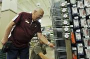 John Ehlers, fishing outfitter, stocks shelves at the Lone Tree Cabela's in preparation fot the grand opening Aug. 15.