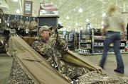 Employee Kirby Boos demostrates a duck call from a sit-in blind in the new Cabela's in Lone Tree, slated to open on Aug. 15.