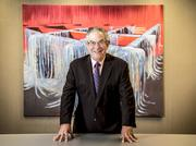 "Alan Kluger with a painting by Fernando Canovas ""Untitled - Scaffold Series"", at his law offices in Miami."