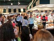 Orange County Comptroller Martha Haynie was offered the first slice of parmesan cheese as The Fresh Market store in Mills Park official opened to the public.