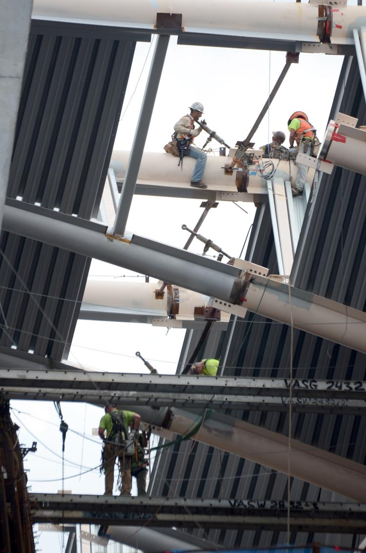 Construction crews work at the uppermost level of the Dr Phillips Performing Arts Center. The building is just over a year away from its targeted completion date.