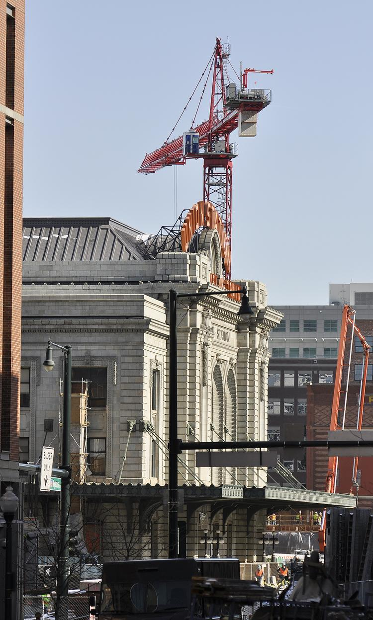 A view from the south side of Denver Union Station  with a glimpse of one of six cranes building apartment and office buildings near.