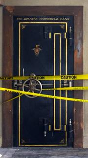 A door labeled The Japanese Commercial Bank is cordoned off with yellow tape in the Pacific Commercial Building in Seattle's Pioneer square