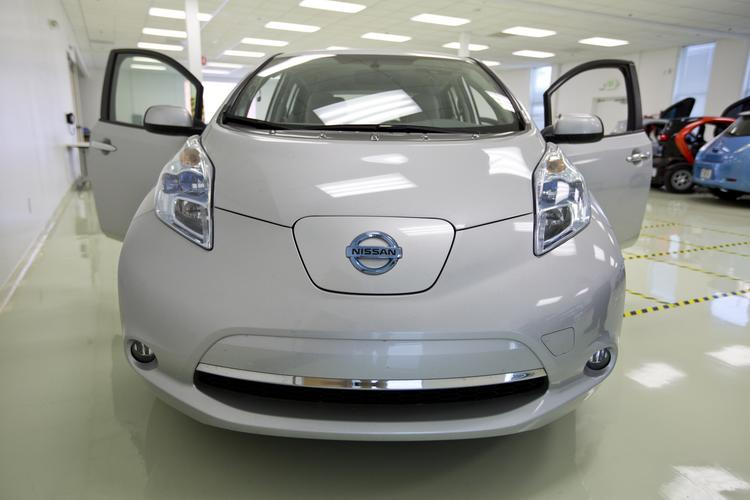 A front-end view of a Nissan Leaf, the all-electric car first released in 2010 is plugged into a charger underneath the Nissan logo at the bottom of the hood.