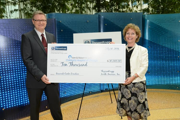 ThyssenKrupp North America CEO Torsten Gessner (left) presents a check to Mary J.C. Hendrix of Lurie Children's Hospital.