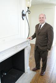 Bryce Baker, vice president-corporate real estate for Security National Capital Inc., a subsidiary of Security National Financial Corp., seen next to the 19th-floor fireplace, says the company is committed to improving the Wichita Executive Centre.