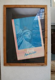 One of several travel posters framed alongside the pool area.
