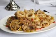 The crispy fried calamari with roasted garlic butter, hot pepper, pimento and pepperoncini. A grilled lemon completes the presentation.