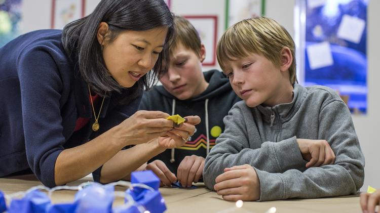 Kiwi Crate CEO Sandra Oh Lin works with brothers Jimmy, left, and John Miller during a craft esting session in Mountain View.