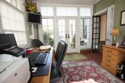 A sun room in the home is used as an office.