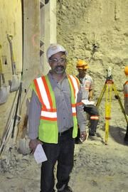 Reporter Oscar Pedro Musibay next to the crew that is cutting an access passage connecting the two tubes inside the PortMiami Tunnel.