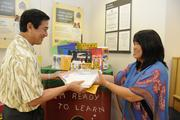 Lance Mizumoto, left, executive vice president, chief banking officer for Central Pacific Bank, hands donated school supplies to Jan Harada, president and CEO of Helping Hands Hawaii. Throughout July, Central Pacific Bank collected school supplies at its 34 branches statewide.