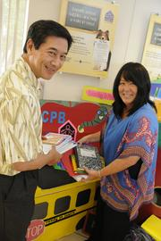 Lance Mizumoto, left, executive vice president, chief banking officer for Central Pacific Bank and  Jan Harada, president and CEO of Helping Hands Hawaii organize school supplies been donated by people at the CPB branch on Kapahulu Avenue. Throughout July, Central Pacific Bank collected school supplies at its 34 branches statewide.