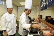 Chef Erwin Manzano of Hy's Steak House, left, and Executive Sous Chef Michael Arita of the Pacific Beach Hotel make up some omelets inside the Finance Factors branch on Bishop Street for a VIP seating at the company's 18th-annula charity breakfast. This year's proceeds will go to Lanakila Meals on Wheels.