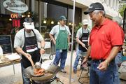 Dixon Bautista, left, systems analyst for Finance Factors, cooks up Portuguese sausage as David Kamimura, executive vice president and chief lending officer for Finance Factors, looks on at Finance Factors' 18th-annual charity breakfast held outside the company's Bishop Street building. This year's proceeds will go to Lanakila Meals on Wheels.