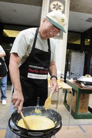 Howard Murai, president and chief operating officer for Finance Realty, an affiliate of Finance Factors, scrambles up an order of eggs for Finance Factors' 18th-annual charity breakfast held outside the company's Bishop Street building. This year's proceeds will go to the Lanakila Meals on Wheels.