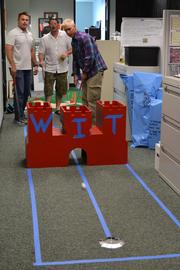"""Nordic PCL held a """"Hallway Golf"""" fundraiser for Aloha United Way turning their Downtown Honolulu office on Alakea Street into a miniature golf course. Teams and departments would sponsor and create their own themed holes, often on based on their current projects. From left, Nordic PCL's Bryce Gruba, purchasing manager; Jody Beckcom, project engineer and Justing LaBore, superintendent, check for a hole-in-one."""