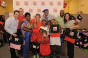 """Cannon, shown here with Matthew Tomalewicz, Office Depot District Manager; Kevin Bowen, Office Depot Store Manager; Essie """"Big Mama"""" Reed and the children of Big Mama's Team of Life Organization; Mary Wong, Office Depot Foundation President; Michael Allison, Executive Vice President of Human Resources for Office Depot; and Christine Buscarino, Vice President of Marketing for Office Depot; assisted in handing out specially designed sackpacks to nonprofit organizations, schools and agencies that serve children in need in the Fort Lauderdale area."""