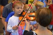 This little girl wanted to try the violin.