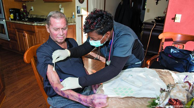 Tiffany Anderson, a nurse with Visiting Nursing Association, places an IV for patient William Wind, who receives home care weekly from the agency.