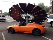 Joseph Hui's Tesla Roadster, with his lotus flower solar panel attached to what he calls his Lotus Mobile car. The solar doesn't run the car, electric does. But solar is a possibility to run a car.
