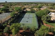 Toward the front of the property sits a tennis court.