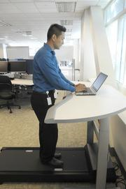 Tristan Aquino works at a treadmill station at the Sutter Health Shared Services Center. There are no cubicle walls or private offices.
