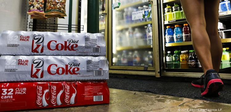 Cases of Coca-Cola Co. and Diet Coke soda are displayed for sale as a customer browses refrigerated beverages at a convenience store in Redondo Beach, California, U.S., on Monday, July 15, 2013.