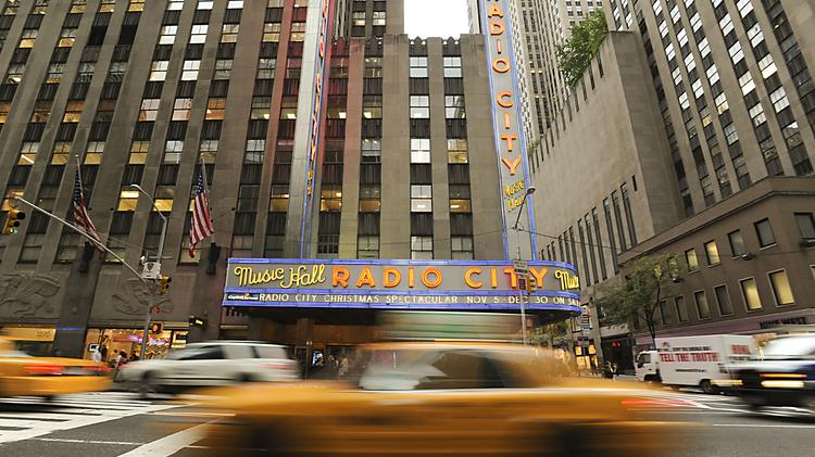 A taxi passes Radio City Music Hall in New York.