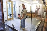 A worker installs a temporary safety strip on the glass for the welcome center at Charlotte Law's new space uptown. Eventually, the glass will be frosted.