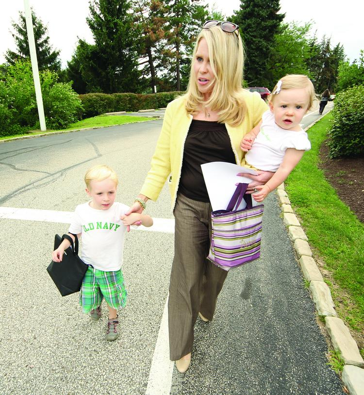 Hollie Geitner has her children, Preston, 4, and Peryn, 1, in tow on Aug. 6 after picking them up at day care.