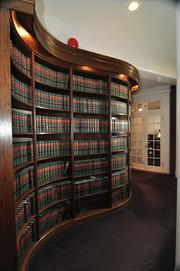 A curved bookcase holds law books for Deily Mooney & Glastetter LLP, a law firm that currently occupies the building. Founding principal Jon Deily owns the building.