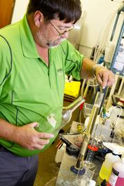 Dave Crosby at Plum Run Winery tests the sugar level in a batch of wine he is making.