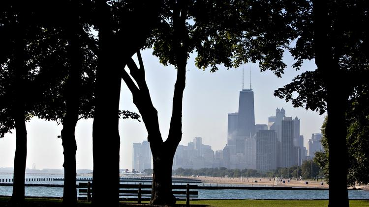 The  city skyline stands in the background of trees in Lincoln Park in Chicago. Photographer: John Zich/Bloomberg