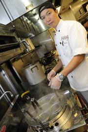 Chef Derek Vong cooks up yakisoba noodles in the kitchen of the new Panya Bistro in the Hokua.