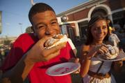Kameron Knapp of Marcus Corp. and Migena Lybeshari - a student at UW-Madison - eat cream puffs.
