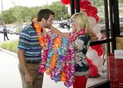 Opening day customer Chase Vincent gets a lei from Micaiah Galpin.