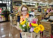 Laura Capps checks out with a bag full of flowers.