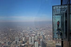 Visitors stand on the glass balcony at the skydeck of the Willis Tower in Chicago. Willis Tower, formerly named the Sears Tower, is the tallest building in the U.S. and one of the most popular tourist destinations in Chicago with more than one million visitors to its observation deck each year.